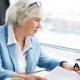mulher idosa caucasiana de cabelos brancos e blazer azul claro mexendo em notebook